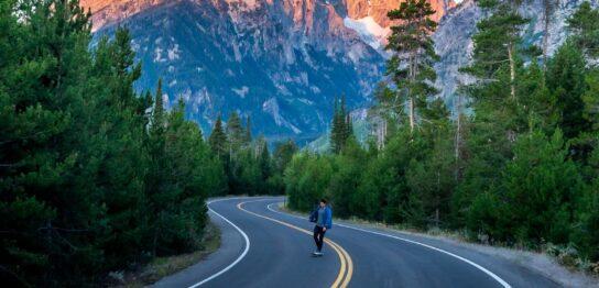 person in black jacket and blue denim jeans walking on gray asphalt road